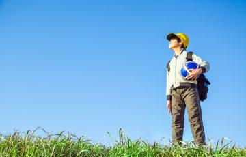 サッカーボールを持ち遠くを見つめる小学生の男の子