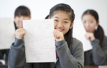 テストを持ち微笑む中学生